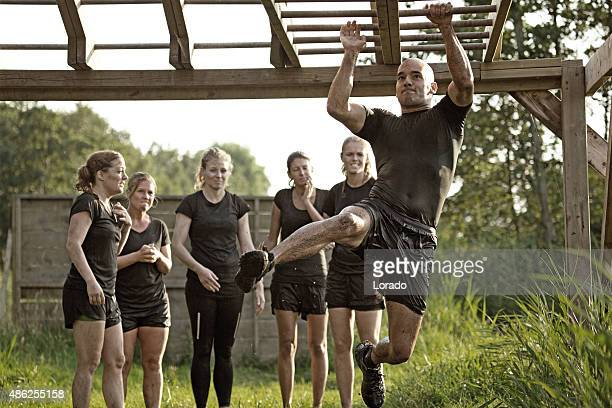 man crossing monkey bars in front of group of women