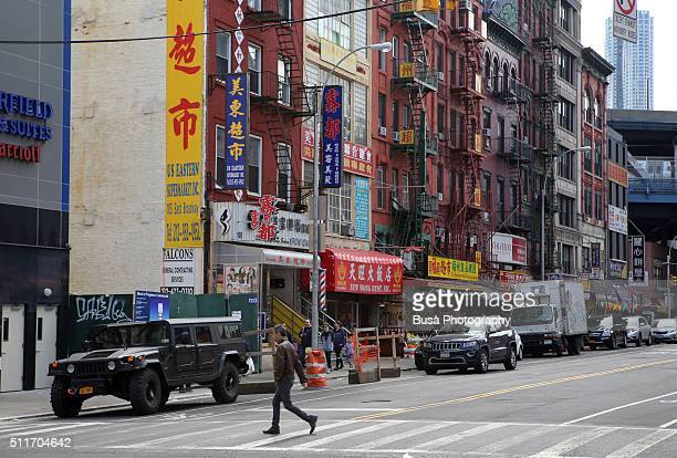 Man crossing street in Chinatown, Lower Manhattan, New York, USA