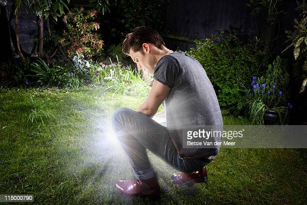 Man crouched looking at light shining.
