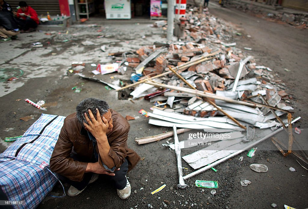 A man crouches near his damaged home in BaoXing county, one of the hardest hit areas of the earthquake zone, on April 22, 2013 in China. A powerful earthquake struck the steep hills of China's southwestern Sichuan province on the morning of April 20, leaving hundreds dead and thousands injured.