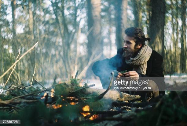 Man Crouching By Campfire In Forest
