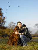Man crouching down beside dog in park, portrait