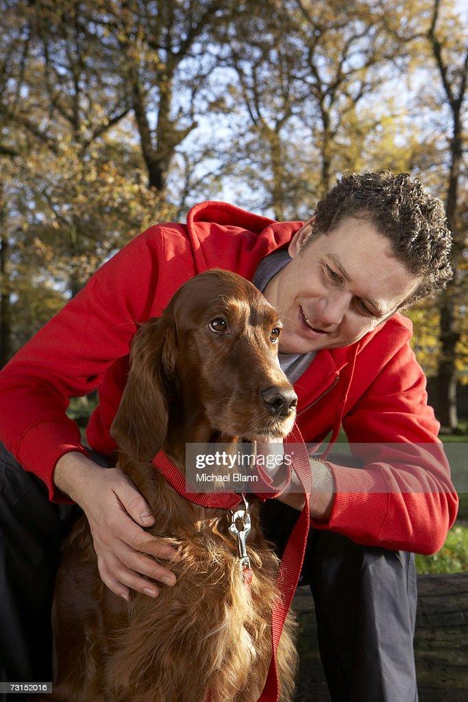 Man crouching down, stroking dog : Stock Photo