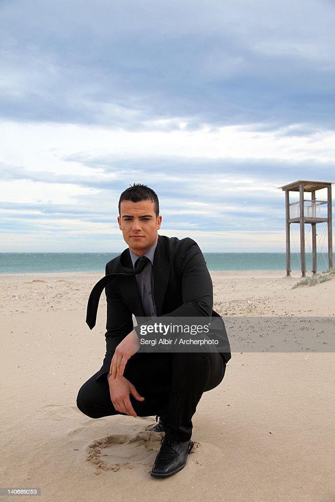 Man crouching on beach : Stock Photo