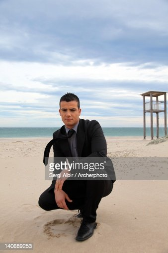 Man crouching on beach : Stock Photo