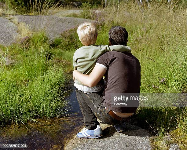 Man crouching on rock beside stream with son (3-5) on knee, rear view