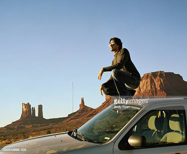 Man crouching on roof of car, looking at rock formations, side view