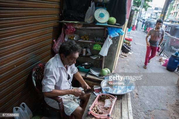 A man cuts betel nuts at a stall in the Pettah neighborhood of Colombo Sri Lanka on Thursday April 20 2017 The Central Bank of Sri Lanka is scheduled...