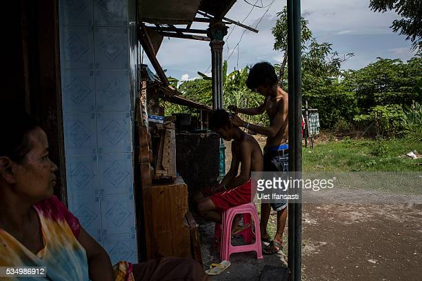 A man cuts his brothers hair in front of their house in Merisen Village on May 27 2016 in Sidoarjo East Java Indonesia The Merisen village was...