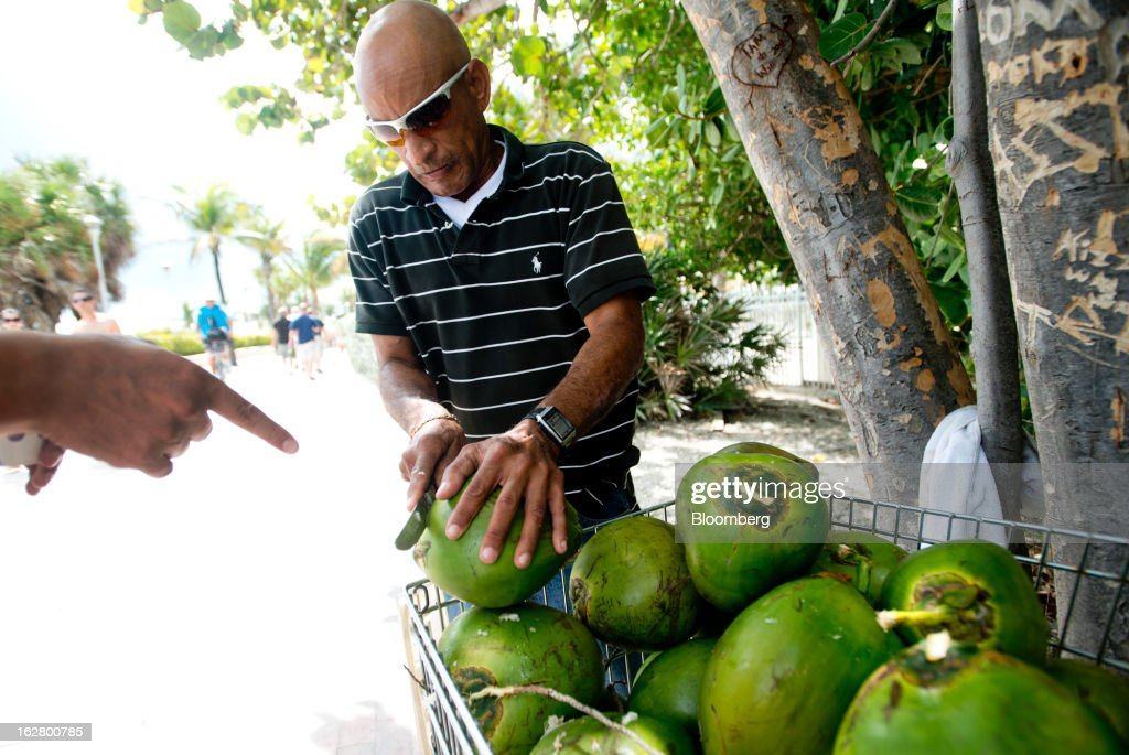 A man cuts the top off a fresh coconut to make a drink for a customer on the boardwalk in Miami Beach, Florida, U.S., on Wednesday, Feb. 20, 2013. U.S. exports in the travel and tourism sector reached $168.1 billion in 2012, up 10.1 percent from the year-ago level of $152.7 billion, according to data released Feb. 22 by the Commerce Department's International Trade Administration. Photographer: Ty Wright/Bloomberg via Getty Images