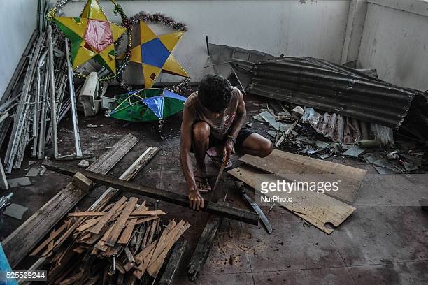 A man cuts up wood he gathered from destroyed houses to use for making fire for cooking inside a birthing institution in Tacloban city Leyte Island...