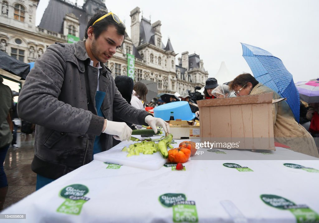 A man cuts vegetables during an event to raise awareness of the food waste on October 13, 2012 at the Place de l'Hotel de Ville in Paris. Five thousand people were invited to enjoy a giant curry prepared using 800 kg of twisted carrots and uncalibrated vegetables that supermarkets refuse to buy from producers and which usually end in disposal. 'While one billion people suffer from malnutrition in the world, a third of the food produced ends up in the trash! I am green since I was 4 years' said Stuart.