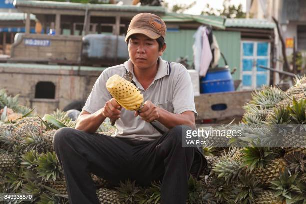 Man cutting a pineapple in the floating market Cai Rang near Can Tho Mekong River Delta Vietnam