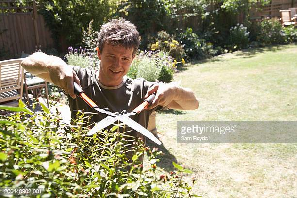 Man cutting bush with garden shears, elevated view