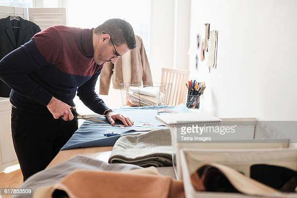 Man cutting clothing in workshop