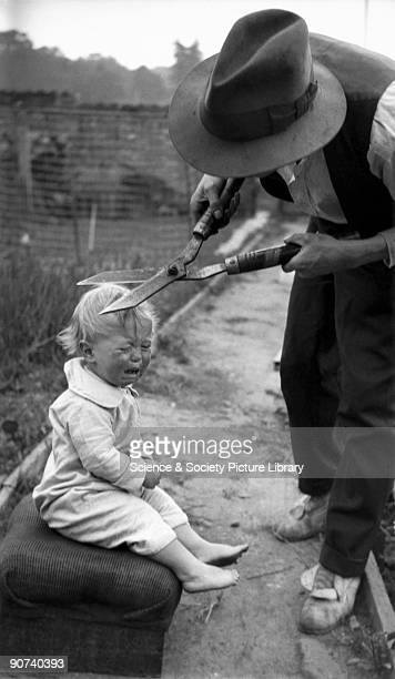Man cutting crying child's hair with garden shears c 1920s