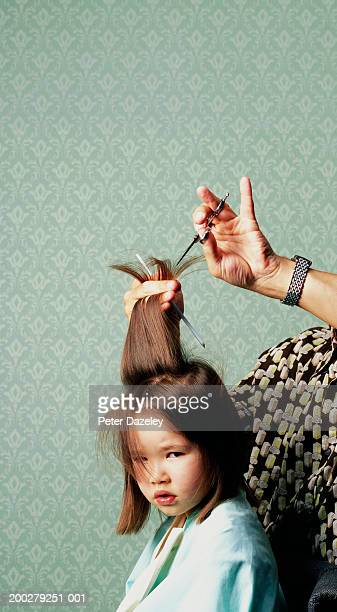 Man cutting girl's (3-5) hair, portrait of girl