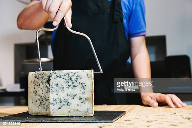 Man cutting gorgonzola in a in a cheese shop