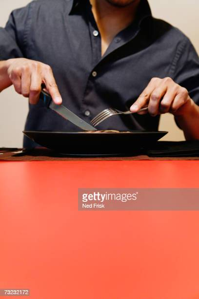 Man cutting meat on plate at table