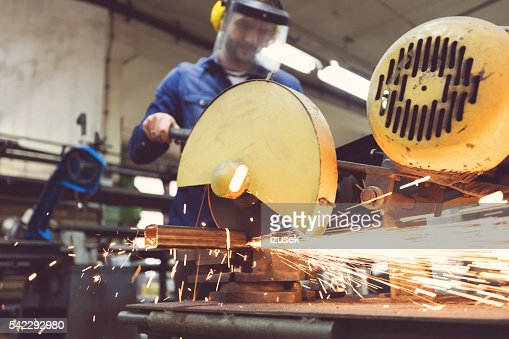 Man cutting metal bar in a workshop, using grinder