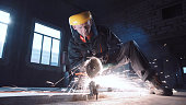 Man wearing protective mask cutting metal with grinder in hangar