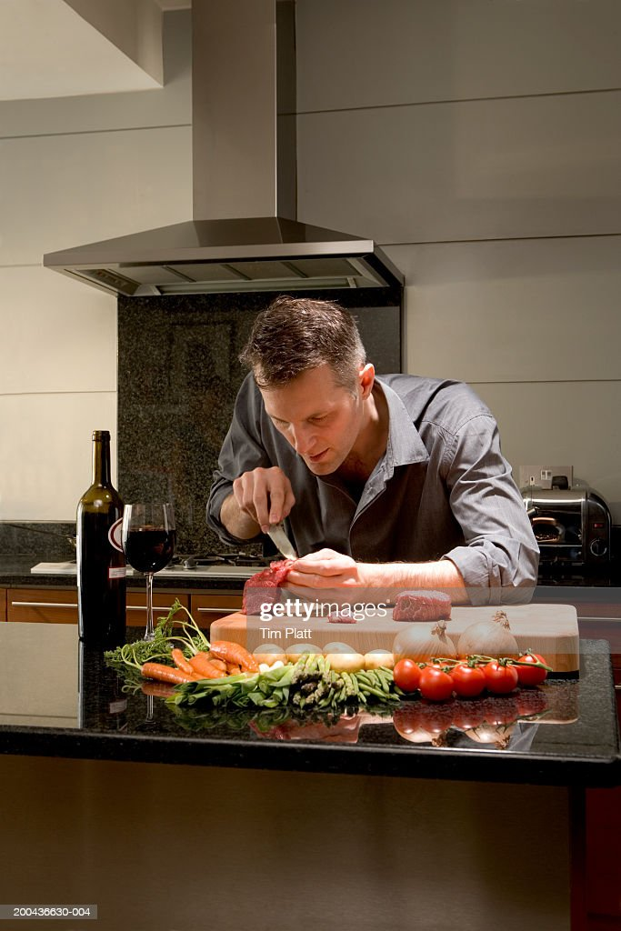 Man cutting piece of meat in kitchen, close-up : Stock Photo