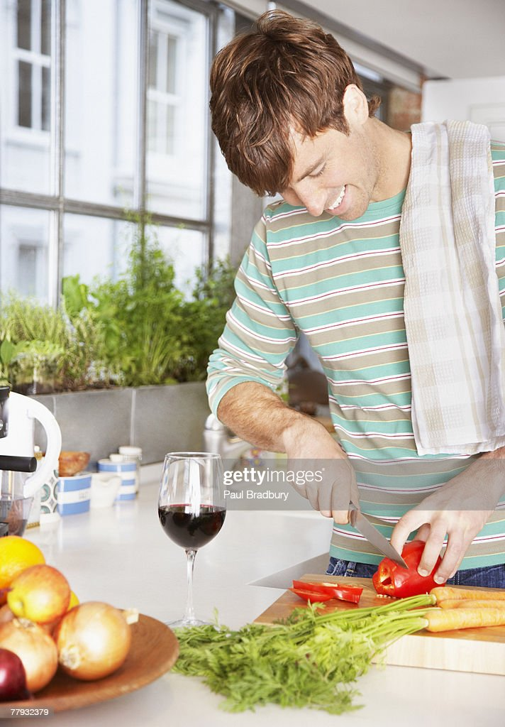 Man cutting red peppers in a kitchen : Stock Photo