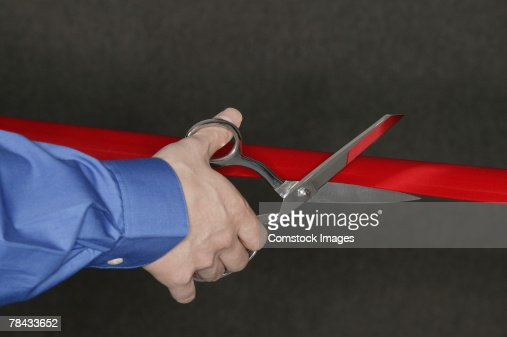 Man cutting red tape