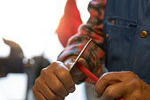 A man is cutting the tip of a pencil off with a knife.