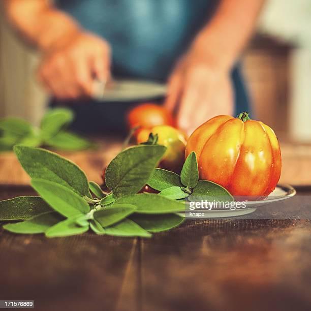 Mann Schneiden von Tomaten in rustikalen Küche