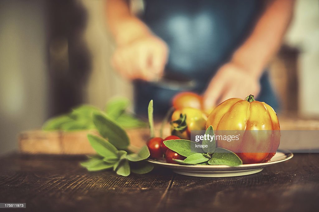 Man cutting tomatoes in rustic kitchen : Stock Photo