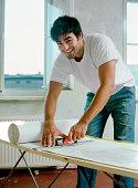 Man cutting wallpaper