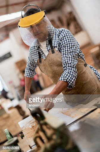 Man cutting wood at the carpentry