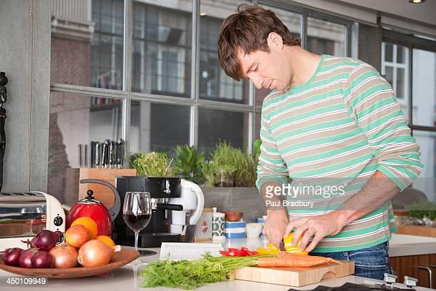 Hombre Cortando amarillo pimientos en una cocina