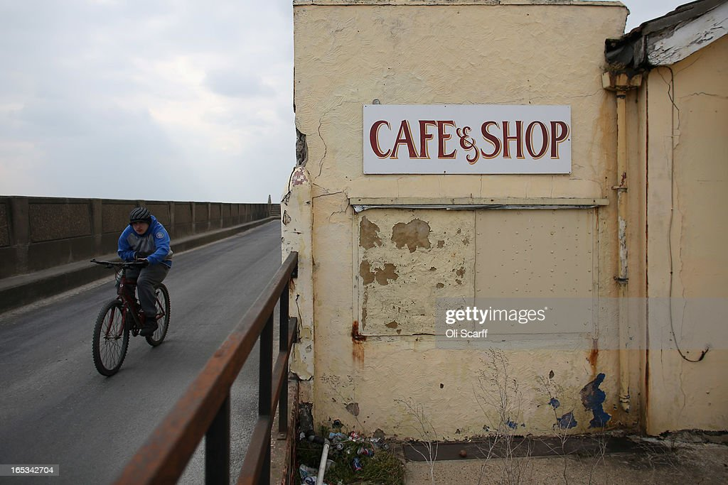 A man cycles a bike in the seaside town of East Jaywick, the most deprived place in England, on April 3, 2013 in Jaywick, England. The Government's 2011 'Indices of Multiple Deprivation' measure ranks Jaywick as the most deprived of all 32,482 small wards in England and Wales. The area also has the greatest number of young people not in employment, education or training; one third of 16 to 24 year-olds claim Jobseeker's Allowance, compared to the national average of 6 per cent. Changes to the benefits and tax system which came into force on April 1, 2013 have included a cut in housing benefit payments for working-age social housing tenants whose property is deemed larger than they need and council tax support payments now being administered locally.