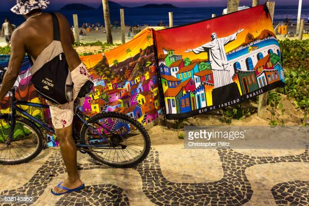 Man cycles along Ipanema beach sidewalk with pareos of scenes of Rio de Janeiro fluterring in the wind.