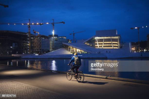 A man cycles along the waterfront opposite the opera house at night in Oslo Norway on Wednesday Sept 20 2017 Norways sovereign wealth fund hit...