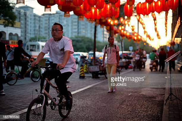 A man cycles beneath lanterns hanging above a street ahead of the Mid Autumn Festival in Beijing on September 26 2012 Traditionally recognized as a...