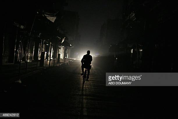A man cycles down a street with no electricity in the besieged rebel bastion of Douma northeast of the capital Damascus on November 19 2014 Douma has...