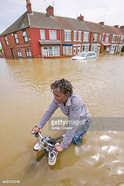 A man cycles down the main street of Toll Bar near Doncaster UK flooded in the June 2007 unprecedented summer floods | Location Toll Bar near...