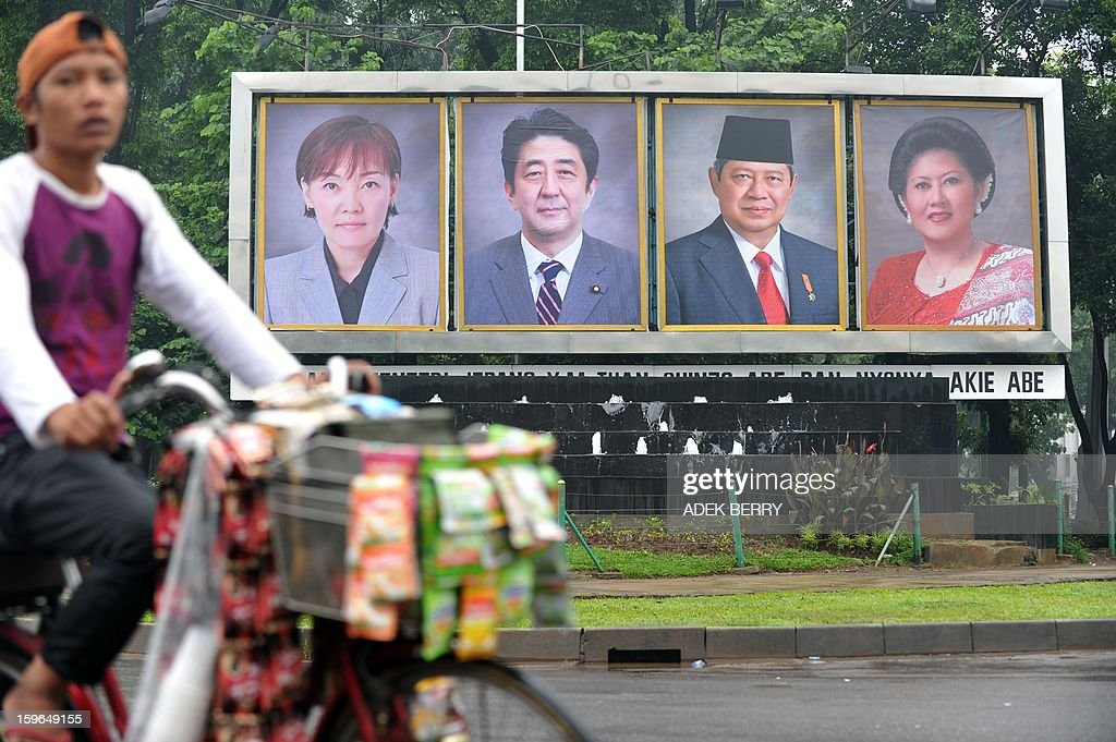 A man cycles in front of photos (back L) of Japanese Prime Minister Shinzo Abe (photos 2nd L) and his wife Akie (photos L) and Indonesian President Susilo Bambang Yudhoyono (2nd R photos) and his wife Ani Yudhoyono (photos R) taken in Jakarta on January 18, 2013. Japan's Prime Minister Shinzo Abe is scheduled to meet Indonesia's President Susilo Bambang Yudhoyono on January 18 during his two-days visit.