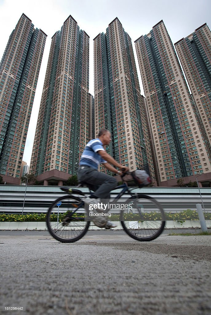 A man cycles in front of residential tower blocks in the Tiu Keng Leng area of the New Territories in Hong Kong, China, on Tuesday, Sept. 4, 2012. Hong Kong will boost the supply of homes and give preference to local buyers as it seeks to cool housing prices that have surged to the world's most expensive, fueled by record-low interest rates and Chinese investment. Photographer: Daniel J. Groshong/Bloomberg via Getty Images