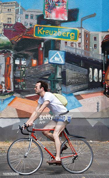 A man cycles past a building with a street scene painted on the wall in Berlin's Kreuzberg district on July 5 2010 AFP PHOTO / DAVID GANNON