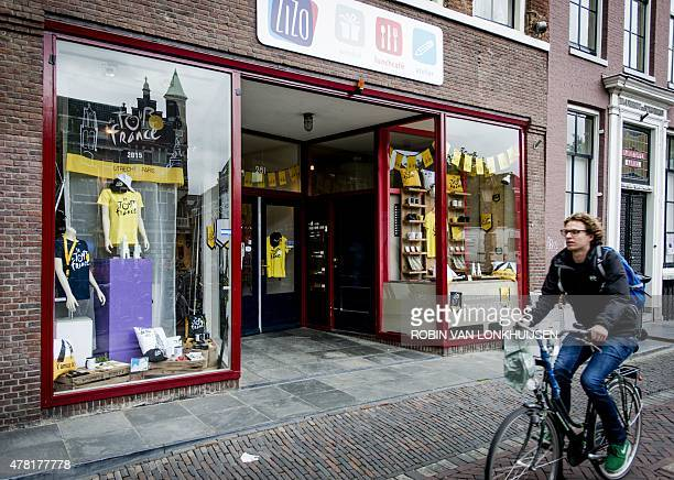 A man cycles past a cafe displaying Tour de France items for sale ahead of the upcoming Tour de France cycling race in downtown Utrecht on June 23...