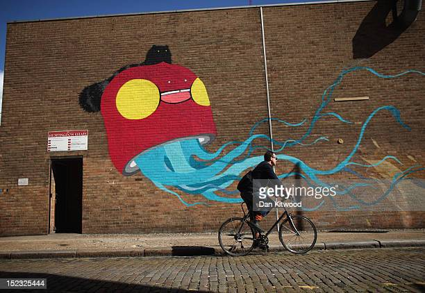 A man cycles past a large piece of street art near Brick Lane on September 18 2012 in London England