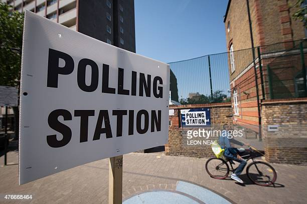 A man cycles past a polling station in the Tower Hamlets borough of London on June 11 2015 as local elections take place Voters went to the polls to...