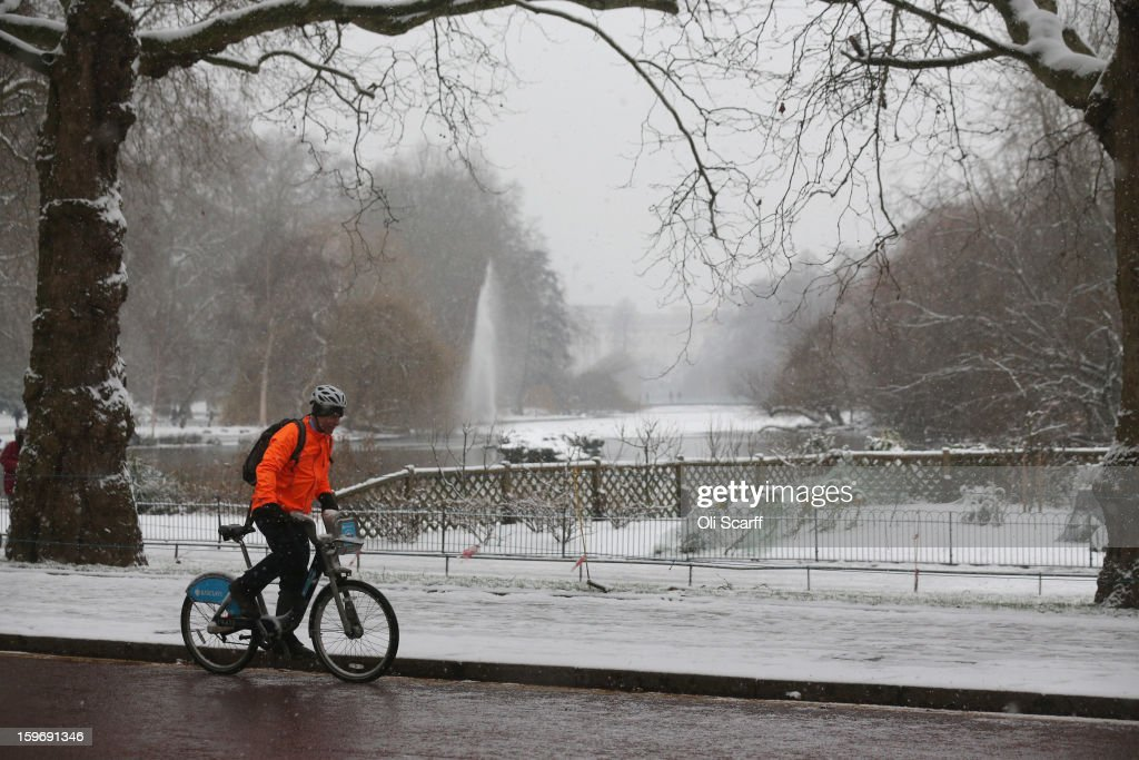 A man cycles past a snow-covered St James's Park on January 18, 2013 in London, England. Widespread snowfall is affecting most of the UK with school closures and transport disruption. The Met Office has issued a red weather warning for parts of Wales, advising against all non-essential travel as up to 30cm of snow is expected to fall in some areas today.