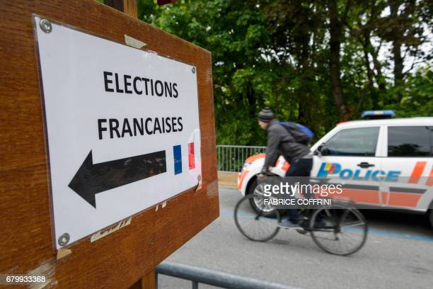 A man cycles past a Swiss police car next to a card reading in French 'French Elections' at the entrance of a polling station for French citizens...