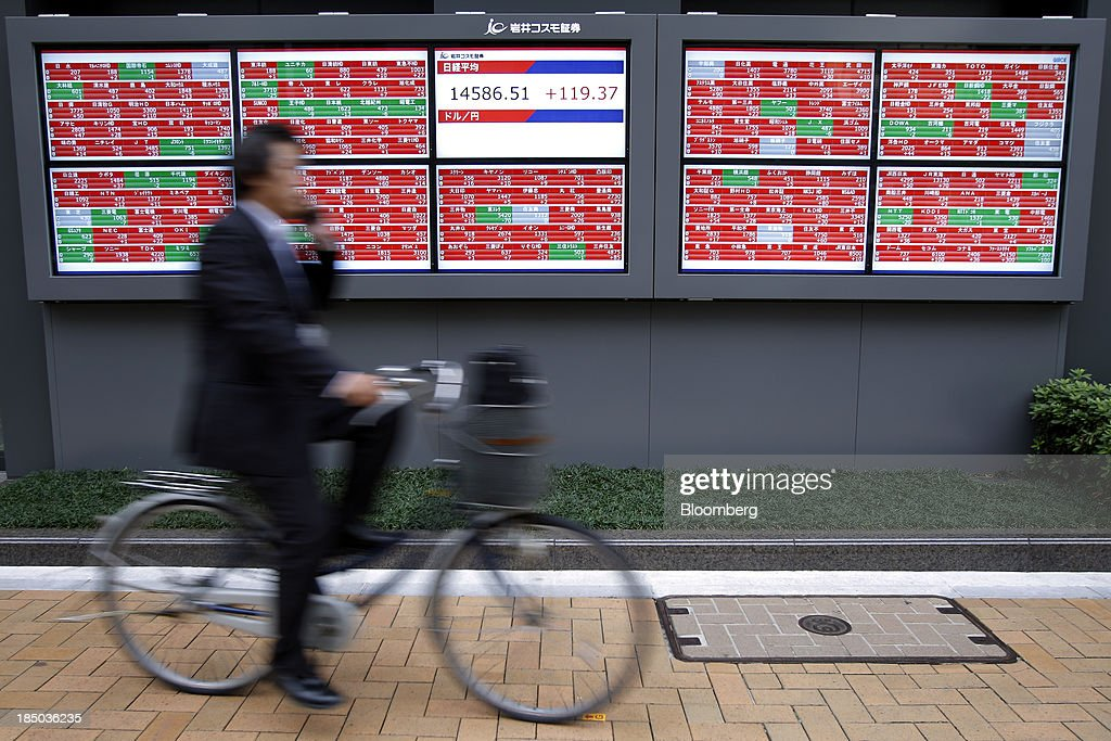 A man cycles past an electronic stock board displaying the closing figure of the Nikkei 225 Stock Average, center, in Tokyo, Japan, on Thursday, Oct. 17, 2013. Japanese shares rose, with the Topix index climbing to a three-week high, after the U.S. Congress voted to end the government shutdown and raise the debt ceiling, ending the nation's fiscal impasse. Photographer: Kiyoshi Ota/Bloomberg via Getty Images