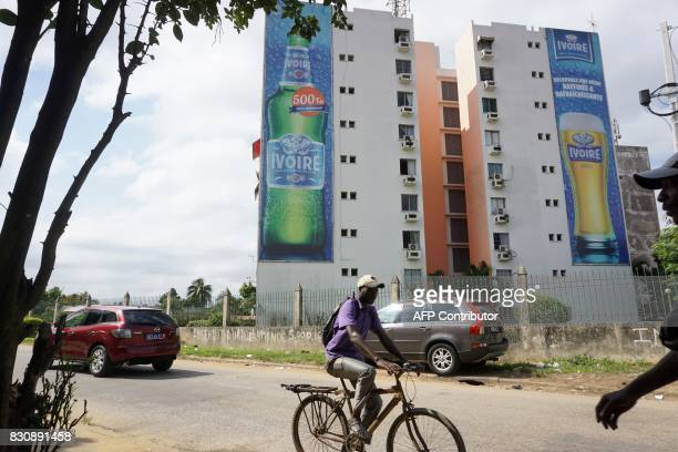 A man cycles past apartment buildings displaying large advertisement banners for Ivoire lager beer in Abidjan on July 13 2017 On posters and huge...